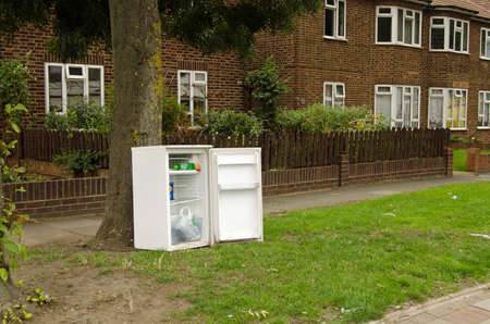 LONDON, UK - SEPTEMBER 5, 2015:  A refridgerator with some rubbish abandoned on the grass verge between the pavement and some flats on a main road in Dagenham, East London on a cloudy day in September.