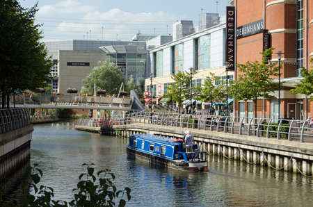 READING, UK - SEPTEMBER 10, 2015:  A narrowboat barge sailing along the River Kennet as it passes through the Oracle Shopping Centre in Reading, Berkshire on a Sunny lunchtime in September.