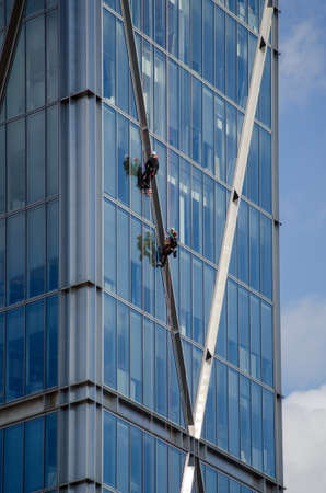 abseil: Abseilers descending down the skyscraper Broadwick Tower in the City of London financial district.  Viewed on a sunny afternoon in late summer. Stock Photo