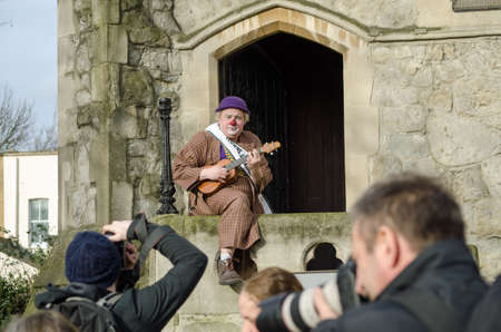 ukelele: HACKNEY, LONDON - FEBRUARY 7, 2016:  A clown playing a ukelele poses for photographers outside All Saints Church in Haggerston ahead of the annual Clown Service in memory of Joseph Grimaldi - known as the King of Clowns. Editorial