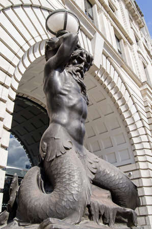 merman: View of a merman Triton holding up a lamp outside Triton House on Finsbury Square in Islington, Central London.  The mythical Greek god is the messenger of the sea.