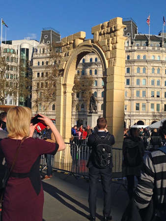 arch: LONDON, UK - APRIL 19, 2016: Crowds photographing and enjoying a recreation of the Arch of Triumph from Syrias ancient city of Palmyra.  The arch has been recreated by 3D printing and will travel the world.