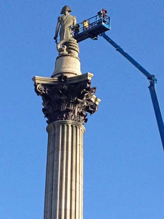 greenpeace: LONDON, UK - APRIL 19, 2016:  Engineers using a tall cherry picker inspect the statue of Lord Nelson on top of the tall column in Trafalgar Square, London.  The day before, the landmark had been scaled by Greenpeace activists who placed a mask on the stat