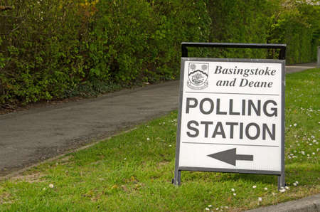 grass verge: BASINGSTOKE, UK - MAY 5, 2016:  A sign pointing towards a polling station in the Hampshire borough of Basingstoke and Deane on election day.