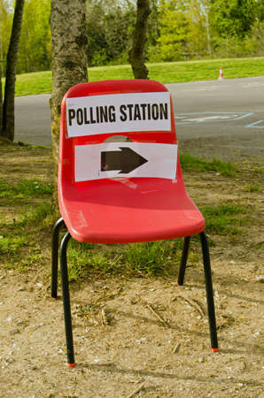 encuestando: A small childs stacker chair with a sign pointing towards a polling station at a primary school on election day in Basingstoke, Hampshire, UK.
