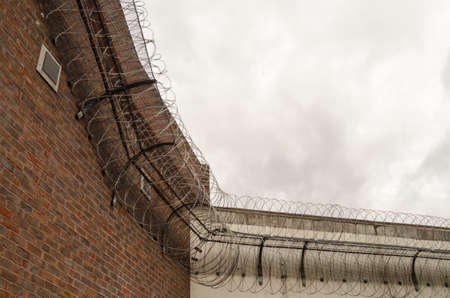 berkshire: Looking up at the tall wall surrounding Reading Prison with razor wire coiled around the top to deter escape.  Berkshire.  The prison once had playwright Oscar Wilde as an inmate..