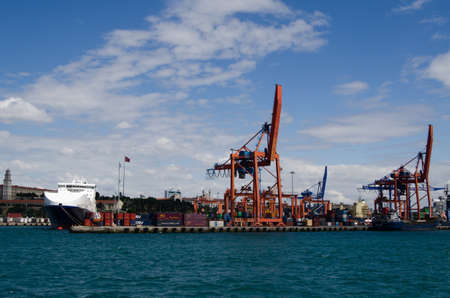 ISTANBUL, TURKEY - JUNE 8, 2016: Dockside cranes, anchored ships and containers at the quayside at Haydarpasa Port on the Asian side of the Bosphorus in Istanbul.  Viewed from a ferry on a sunny Summer afternoon.