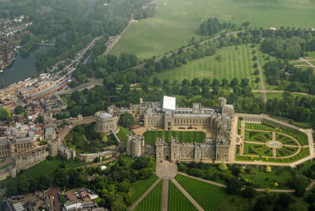 View from a plane of the historic Windsor Castle, home of Queen Elizabeth II in Royal Berkshire.  The River Thames passes to the left hand side and castle grounds stretch to the edge of the image.  Cloudy Summer morning in June 2016. Editorial