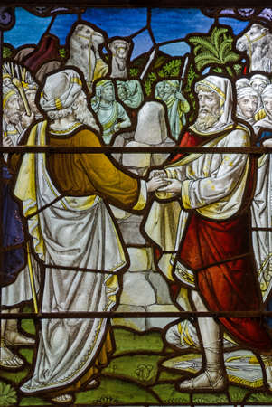headress: A Victorian stained glass window showing two men making an emotional agreement or Mizpah as described in the Old Testament parable of Jacob and Laban. Historic window on public display over 100 years.
