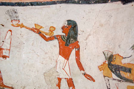 Ancient Egyptian mural showing a priest carrying an incense burner over a mummy.  Ancient Egyptian tomb of Amenemonet on the West Bank of the Nile at Luxor, Egypt.  Historic painting, thousands of years old.