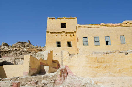A traditional mud brick home painted yellow with some elegant detail in the village of Qurnet Murai.  The house is one of many built over the top of Ancient Egyptian tombs on the West Bank of the Nile in Luxor, Egypt.