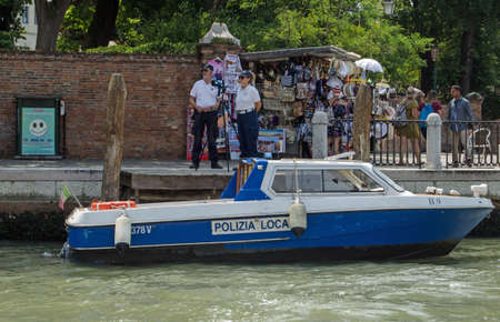 VENICE, ITALY - JUNE 13, 2017:  Two police officers operating a speed trap beside a busy stall selling tourist souvenirs on the Grand Canal in Venice. Editorial