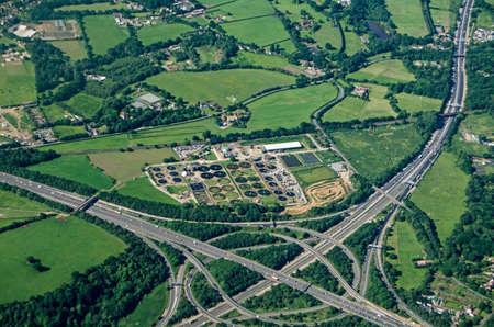 Uitzicht vanuit het vliegtuig op het knooppunt Thorpe Interchange tussen de snelwegen M25 en M3 in Zuidwest-Londen. Een rioolwaterzuiveringsinstallatie van Thames Water ligt vlak naast de drukke wegen in Virginia Water, Surrey.