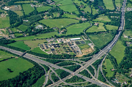 View from a plane of the Thorpe Interchange junction between the M25 and M3 motorways in South West London.  A Thames Water sewage treatment plant is right next to the busy roads in Virginia Water, Surrey. Stock Photo