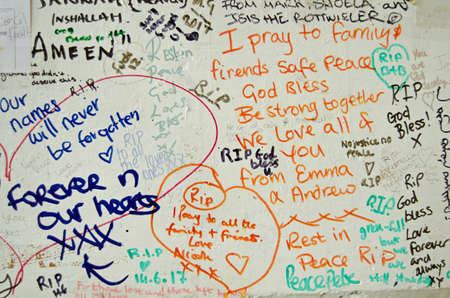 LONDON, UK - JULY 6, 2017:  Memorial messages written on a wall close too the Grenfell Tower block of council flats in which at least 80 people are feared to have died in a fire in Kensington, West London.