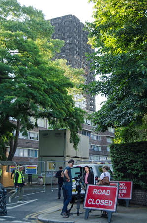 LONDON, UK - JULY 5, 2017:  A Television crew reporting from the site of the Grenfell Tower disaster with construction workers looking on.  At least 80 people are feared to have been killed in a fire at the tower block.