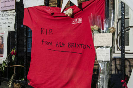 LONDON, UK - JULY 5, 2017: Memorials to victims of the Grenfell Tower fire disasterin Kensington, London.  Among the flowers and messages is a T-shirt from firefighters at Brixton Fire Station, part of the London Fire Brigade.