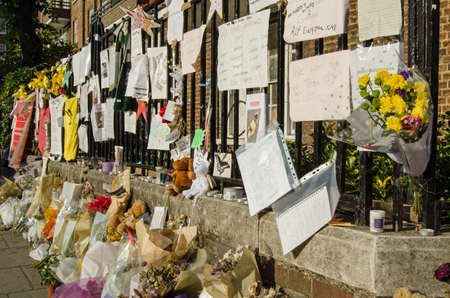 LONDON, UK - JULY 5, 2017: Railings close to Grenfell Tower covered in memorials to those killed and missing.  At least 80 people are thought to have died in the fire in the council tower block of flats in Kensington, London.