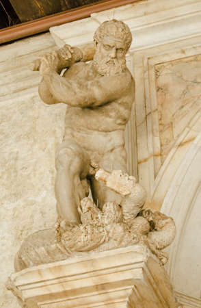 Small statue of Hercules killing the many headed Hydra monster on an exterior wall of the historic Doges Palace in Venice, Italy.