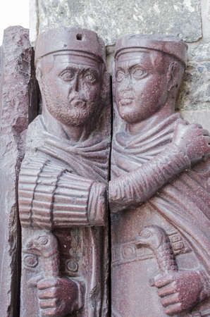 Detail showing two of the characters in the Portrait of the Four Tetrarchs on the exterior of the Basilica di San Marco in Venice, Italy.  Originally carved from porphyry stone in Constantinople, the sculpture was taken by the Venetians in the Renaissance