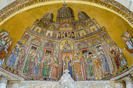 Historic mosaic on the exterior facade of St Marks Cathedral in Venice showing the arrival of the body of St Mark to the city after being smuggled out of Alexandria.  Mosaic over 100 years old, on exterior wall and viewed from public pavement.