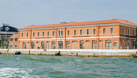 VENICE, ITALY - JUNE 10. 2017: Headquarters of the Venice Port Authority overlooking the Giudecca Canal on a sunny afternoon with the funnel of a large cruise ship to the right hand side. Editorial