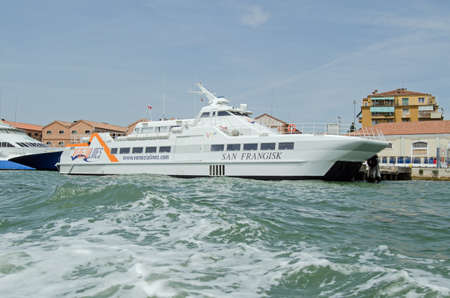 VENICE, ITALY - JUNE 10, 2017: view of the catamaran ferry San Frangisk, part of the Venezia Lines fleet which transports passengers across the Adriatic between Venice and Croatia.  Giudecca canal on a sunny summer afternoon.