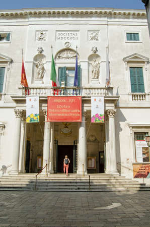 venice: VENICE, ITALY - JUNE 13, 2017:  A woman walking into the historic La Fenice opera house in Venice, Italy on a sunny summer morning.
