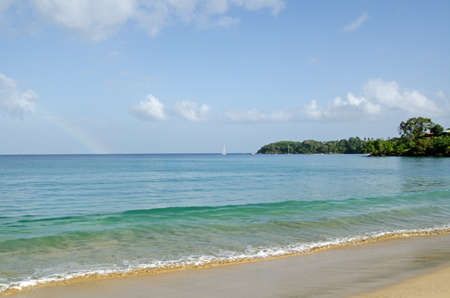 A pale rainbow fades on the horizon during a sunny morning at the beach of Grange Bay, Tobago.  Part of the Caribbean island nation of Trinidad and Tobago.