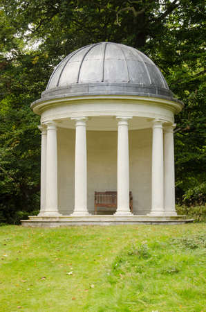 The historic Rotunda with doric columns and a garden bench set in the grounds of Bushy House, once home to King William IV and Queen Charlotte. Historic building, open to the public and hundreds of years old. Stock Photo