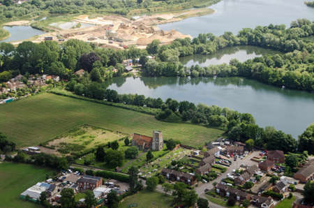 Aerial view on the approach to Londons Heathrow Airport of the parish church of St Michael in Horton near Slough in Berkshire.  Beyond the church is the Cemex cement works. Stock Photo