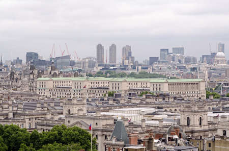 View across the rooftops of Whitehall with the green copper rooftop of the Ministry of Defence dominating the scene.  Barbican tower blocks , St Pauls Cathedral and the City of London in the distance. Stock Photo