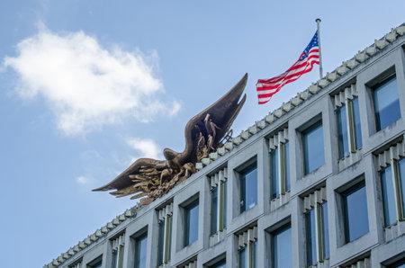 Adler und Flagge auf dem ehemaligen Gebäude der US-Botschaft am Grosvenor Square, Mayfair, London. Das Gebäude wurde vom amerikanischen Architekten Eero Saarinen entworfen und 1960 fertiggestellt.