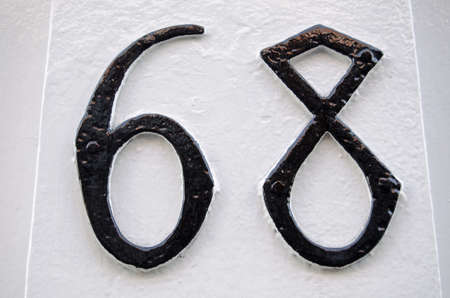 Number 68 in Gothic style carved and painted on the outside of a house in Mayfair, London.