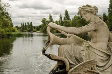 View from a fountain in the Italian Gardens towards the Long Water in Hyde Park on a cloudy day in London. Stock Photo