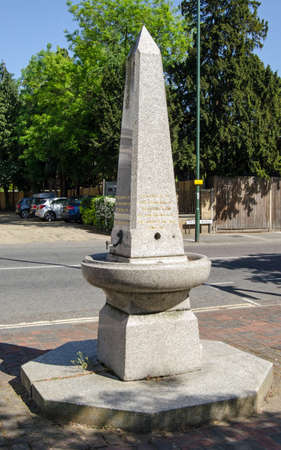 TEDDINGTON, UK - MAY 17, 2018: A granite drinking fountain sculpted in the shape of an Ancient Egyptian obelisk and erected in the middle of Teddington, Middlesex in honour of Queen Victoria's jubilee. On public display ever since.