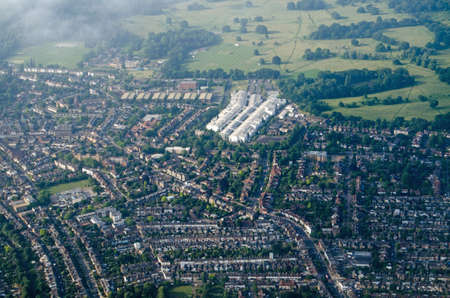 Aerial view of Teddington, Middlesex in the London Borough of Richmond Upon Thames in West London.  The long white building is the National Physical Laboratory and beyond is Bushy Park.  Sunny summer morning.