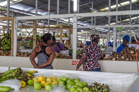 SCARBOROUGH, TRINIDAD AND TOBAGO - JANUARY 11, 2019:  Shoppers perusing the fresh produce on sale at the covered market in Scarborough, Tobago. Standard-Bild - 119635896