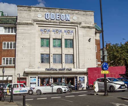 RICHMOND-UPON-THAMES, UK - SEPTEMBER 20, 2015:  Traffic and pedestrians pass the busy junction in front of the historic Richmond Odeon cinema with its amazing Art Deco designs. Standard-Bild - 119635904