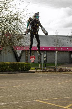 BASINGSTOKE, UK - MARCH 11, 2019:  Gymnast Ryan Hopgood demonstrating a Gravity Industries jet pack by flying over the car park at Basingstoke Leisure Park. Standard-Bild - 119635972