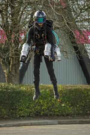 BASINGSTOKE, UK - MARCH 11, 2019: Gymnast turned pilot Ryan Hopgood demonstrating a Gravity Industries jet pack by flying across a car park at Basingstoke Leisure Park. Standard-Bild - 119635987