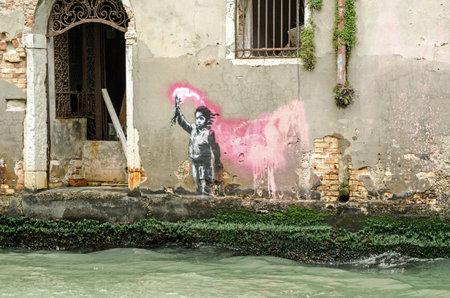 WENECJA, WŁOCHY-15 maja 2019: Wzornikowa sztuka uliczna dziecka noszącego kamizelkę ratunkową i machającego flarą przypisywaną artyście graffiti Banksy. Oglądane z publicznej ulicy z widokiem na Rio di Ca'Foscari w studenckiej dzielnicy Dorsoduro w Wenecji.