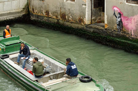 VENICE, ITALY - MAY 15, 2019:  Four men on a contruction workers boat travelling past the stencil street art depiction of a child wearing a lifejacket and waving a flare attributed to graffiti artist Banksy.  Viewed from a public street overlooking the R