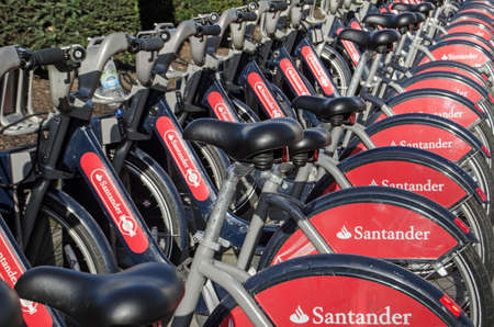 LONDON, UK - JANUARY 28, 2016:  A rack full of public transport bicycles sponsored by the bank company Santander.