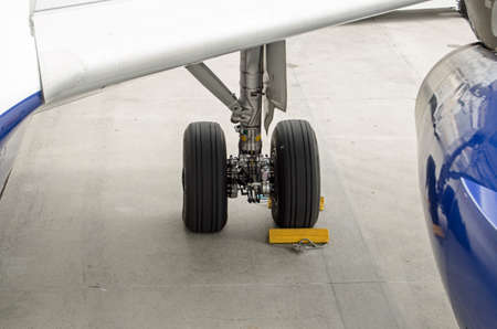 Chocks around the wheels of the undercarriage of an Airbus A319.  They prevent the plane from rolling in the wind.