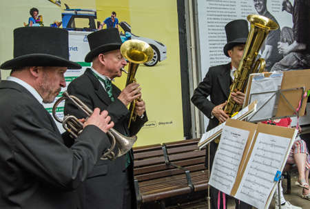 London, UK - June 22, 2019: Musicians playing historic Victorian brass instruments. Members of the band Queen Victoria's Consort playing historic saxhorns and cornets at a public concert.