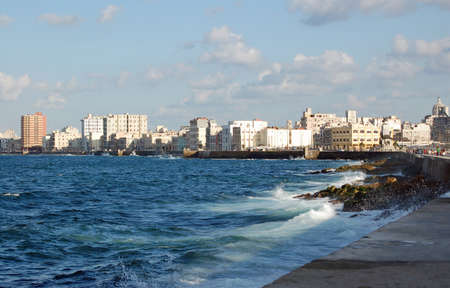 View along the sun drenched Malecon promenade which skirts the Caribbean coastline of Havana, Cuba. Stock Photo