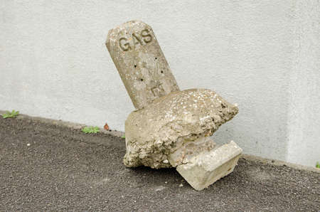 A street marker for a gas main broken and lying in the road like a broken headstone.