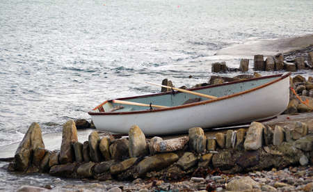 A small rowing boat resting on a slipway.