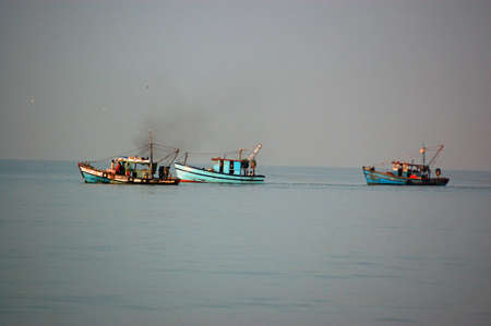THree fishing boats dragging their nets through the calm sea off the coast of Goa, India.